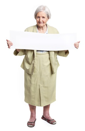 adult 80s: Happy elderly lady holding blank sheet in hands over white Stock Photo