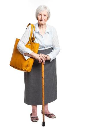 Elegant senior woman with walking stick standing over white