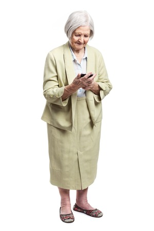 Senior woman using mobile phone while standing over white background photo