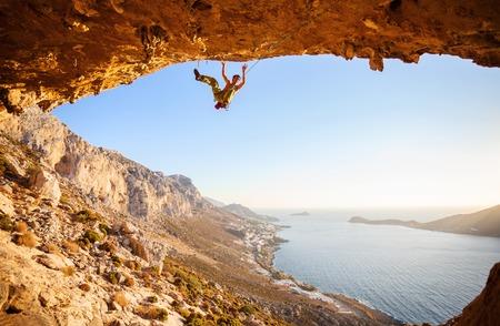 escalada: Escalador masculino acaba cay� de un acantilado mientras que la escalada en roca. Hermosa vista de la costa en el fondo.