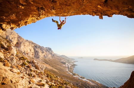 person falling: Male climber has just fell of a cliff while rock climbing. Beautiful view of coast in the background. Stock Photo