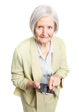 Senior woman holding mobile phone and looking at camera over white photo
