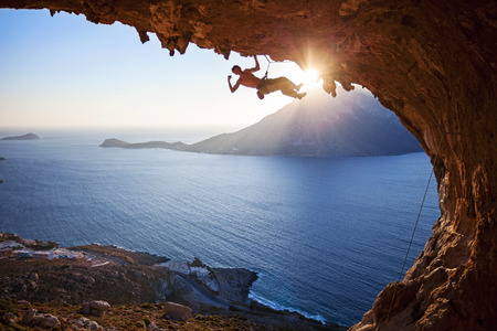 Male rock climber climbing in cave with beautiful view in background