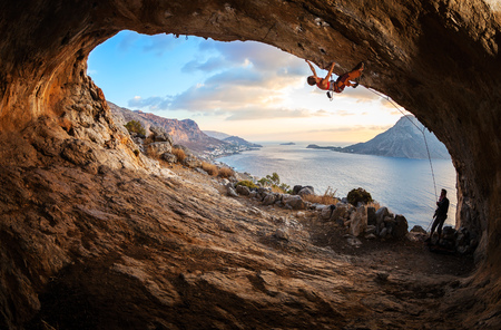 rock cliff: Young woman lead climbing in cave with beautiful view in background Stock Photo