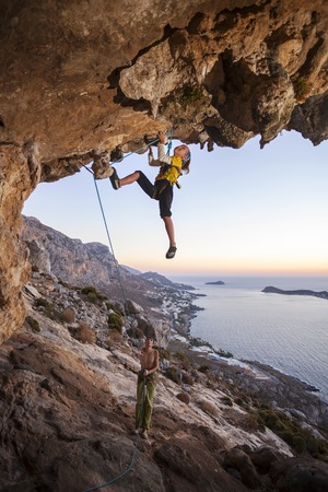 belaying: Seven-year old girl climbing a challenging route, father belaying Stock Photo