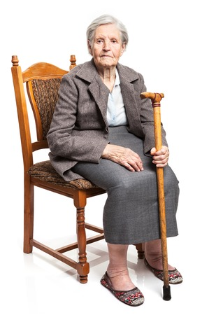 Senior woman with walking stick sitting on chair over white background Stockfoto