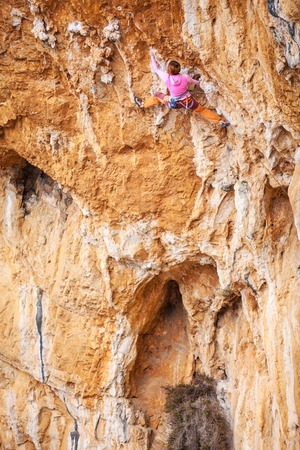 lead rope: Young female rock climber on a cliff face