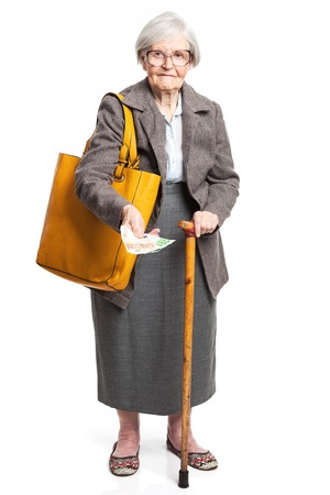 woman holding money: Senior woman holding money while standing over white background