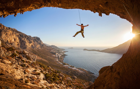 lead rope: Rock climber hanging on rope while lead climbing at sunset