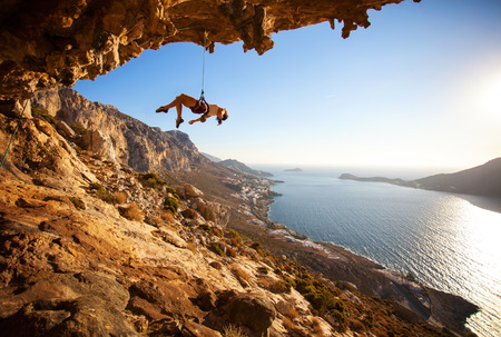 handhold: Female rock climber hanging on rope after unsuccessful attempt to take next handhold on cliff while lead climbing Stock Photo