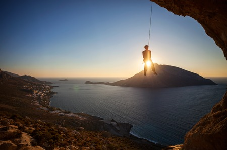lead rope: Rock climber hanging on rope while lead climbing at sunset, with Telendos island in background. Kalymnos island, Greece. Stock Photo