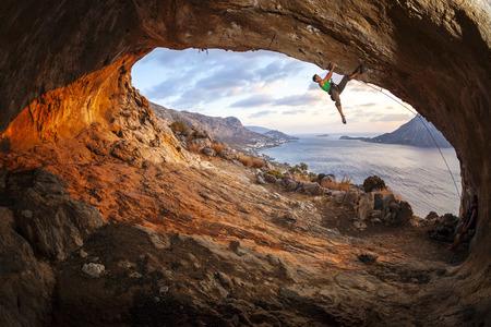 climber: Mannelijke bergbeklimmer het beklimmen langs een dak in een grot bij zonsondergang Stockfoto