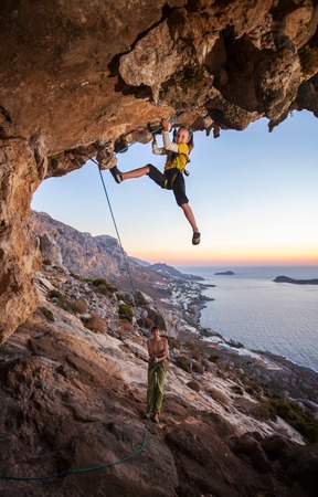 Seven-year old girl climbing a challenging route, father belaying. Kalymnos island, Greece photo
