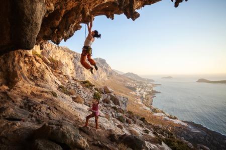 climber: Jonge vrouw lood klimmen op overhangende klif, vrouwelijke partner zekeren Stockfoto