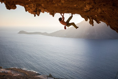 lead rope: Rock climber climbing along a roof in a cave at sunset