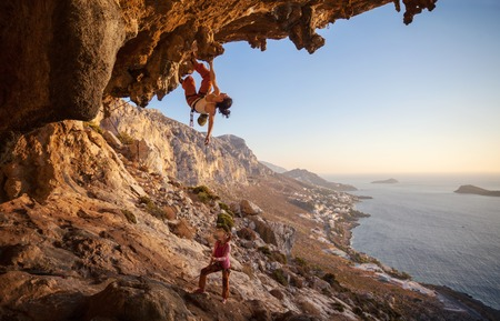 lead rope: Young woman lead climbing along a roof in cave with beautiful view in background Stock Photo
