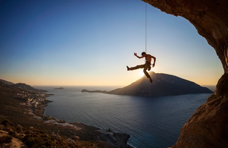 lead rope: Rock climber hanging on rope while lead climbing at sunset, with Telendos island in background