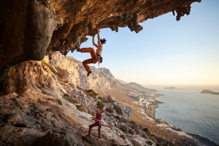 Young woman lead climbing in cave with beautiful view in background Stockfoto