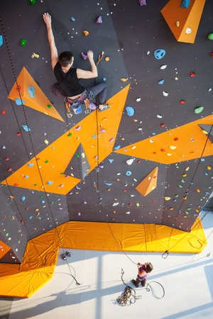 Young man practicing rock-climbing on a rock wall indoors Foto de archivo