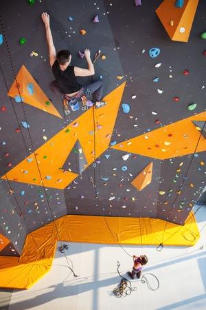rockclimbing: Young man practicing rock-climbing on a rock wall indoors Stock Photo