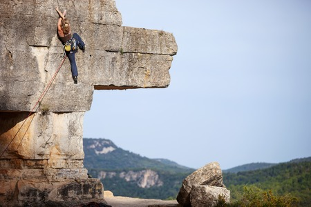 challenge: Young woman climbing a challenging route on a cliff