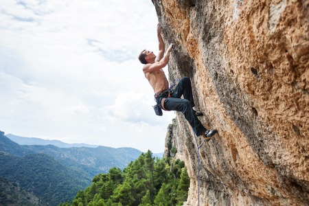 rock cliff: Young male rock climber on challenging route on cliff