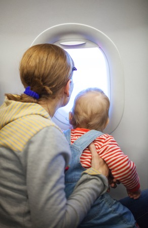 Mother and baby son looking out of window while on board of airplane