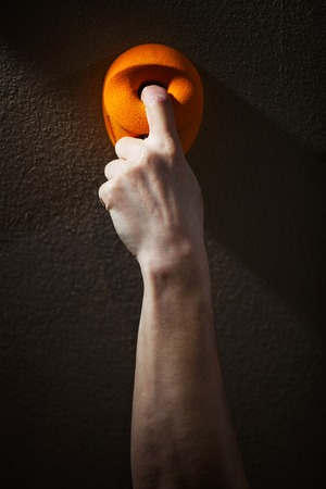 handhold: Cropped view of rock climber gripping handhold with one finger Stock Photo