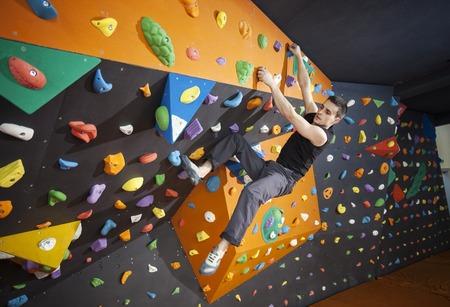 escalando: Joven hombre practicando boulder en el gimnasio de escalada indoor Foto de archivo