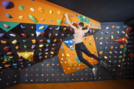 recreational climbing: Young man practicing bouldering in indoor climbing gym