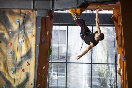 rockclimbing: Young man practicing rock-climbing in indoor climbing gym Stock Photo