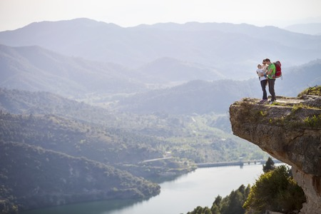 Happy young couple with little son standing on cliff over river