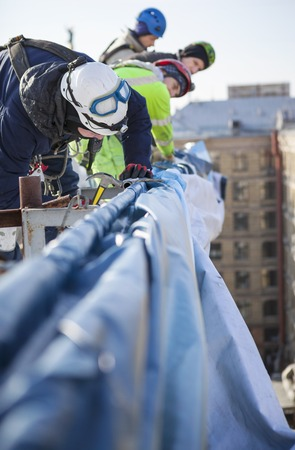 Industrial climbers working on a roof of a building - placing an advertising banner photo