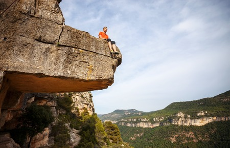edge of cliff: Young pensive man sitting on edge of cliff Stock Photo