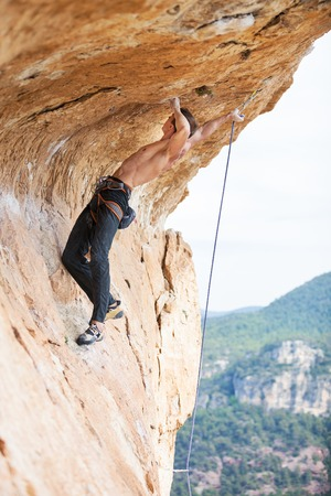 lead rope: Young man clipping rope while clinging to cliff under ledge
