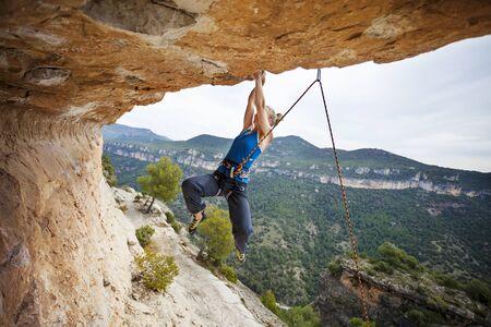 struggling: Woman rock climber struggling to make next movement up