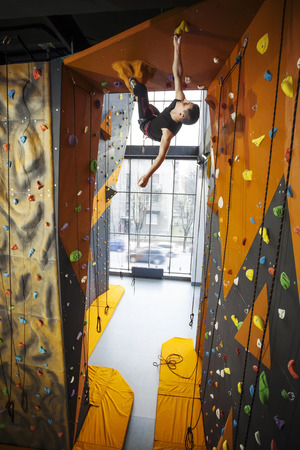 grip: Young man practicing top rope climbing in indoor climbing gym