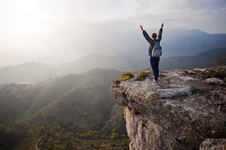 Jonge vrouw die zich op rots met uitgestrekte armen en genieten van uitzicht op de vallei Stockfoto
