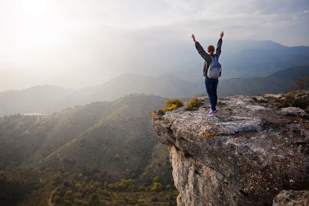 Young woman standing on cliff with outstretched arms and enjoying valley view Foto de archivo