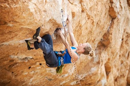 struggling: Young female rock climber struggling to make next movement up Stock Photo