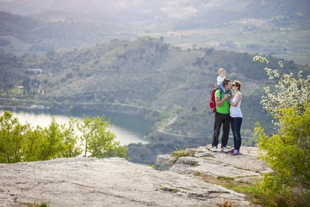 Young couple with toddler boy standing on cliff and kissing photo