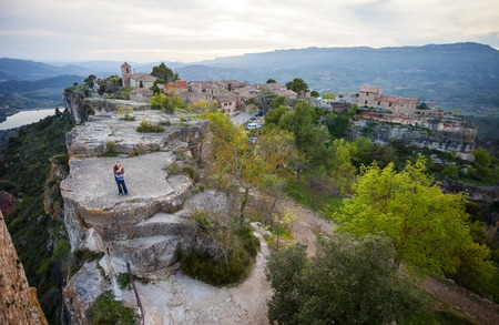 Young couple standing on cliff and enjoying valley view of old village Siurana photo