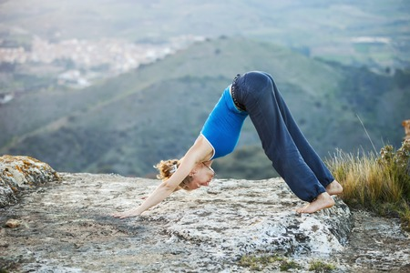 dog rock: Young Caucasian woman performing downward dog yoga pose outdoors Stock Photo