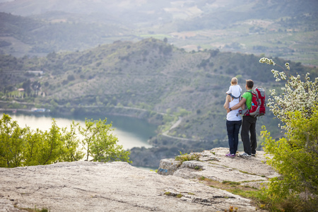 Young couple with toddler boy standing on cliff photo