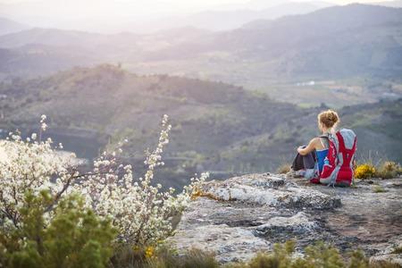 Jonge vrouw toeristische zit op de top van een berg Stockfoto