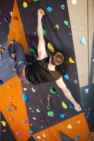 rockclimbing: Young man practicing rock-climbing in climbing gym indoors Stock Photo