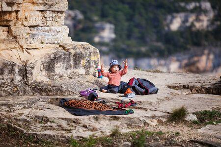 niño escalando: Niño de los escaladores de roca jugando mientras estaba sentado a los pies de una montaña junto a una cuerda de escalada