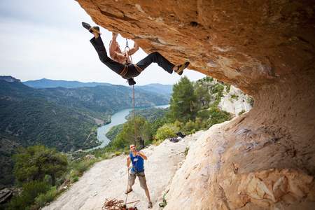 belaying: Young man starting to climb challenging route Stock Photo