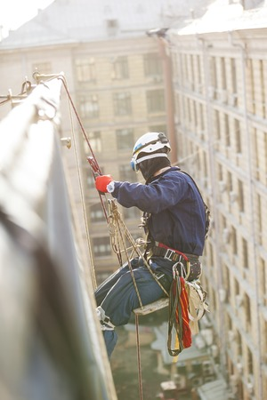 Industrial climber lowering from a roof of a building Standard-Bild