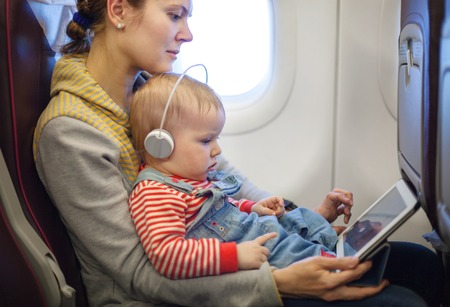 flight: Caucasian mother and toddler son using tablet pc while on board of airplane